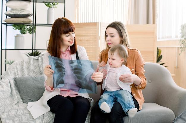 Mooie vrouwenhuisarts die xray beeld tonen aan jonge moeder met vrolijk babymeisje op haar handen