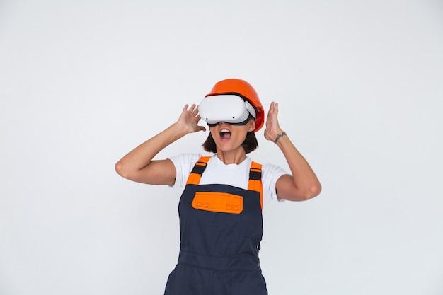 Mooie vrouweningenieur bij het bouwen van een beschermende helm op wit in een virtual reality-bril