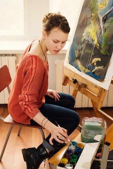 Mooie vrouwenkunstenaar die haar beeld trekt
