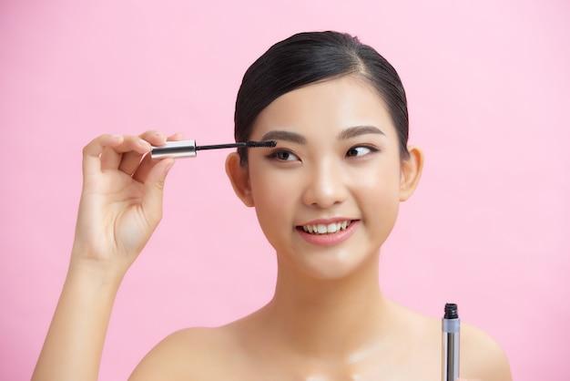 Mooie vrouwenmascara die de schoonheidsconcept van het make-up natuurlijke portret over roze muur toepassen