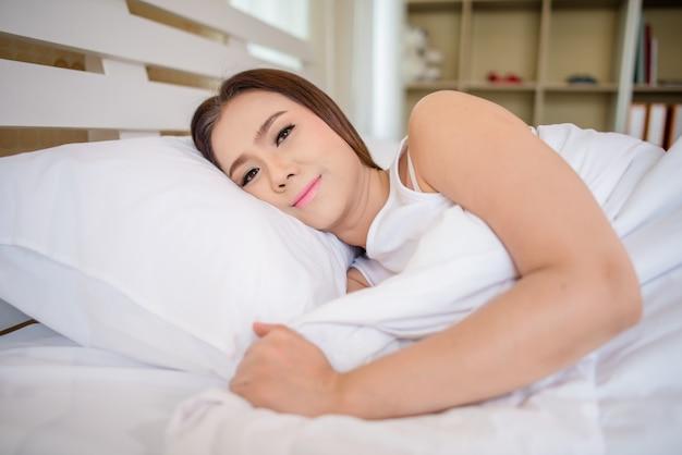 Mooie vrouwenontwaken in haar bed, lui in de ochtend