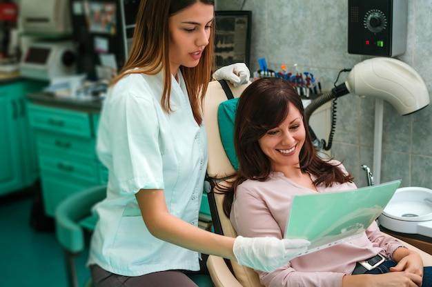 Mooie vrouwenpatiënt die tandbehandeling hebben op het kantoor van de tandarts