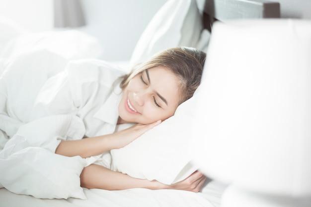 Mooie vrouwenslaap op bed