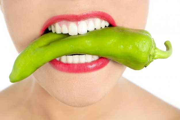 Mooie vrouwentanden die groene paprika eten