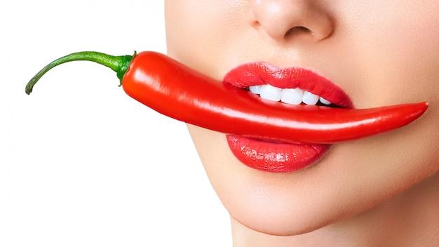 Mooie vrouwentanden die roodgloeiende spaanse peperpeper eten