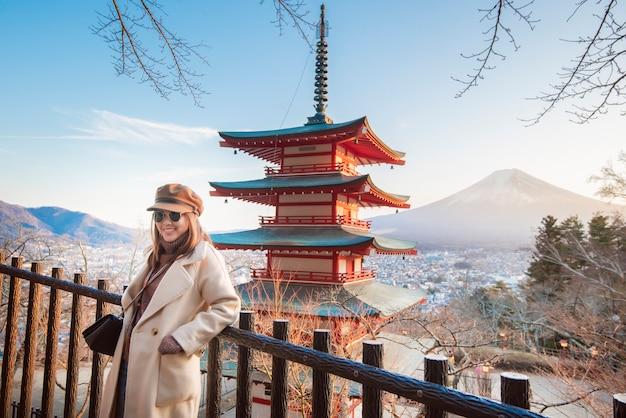 Mooie vrouwentoerist die op chureito-pagode en fuji-berg, japan glimlachen