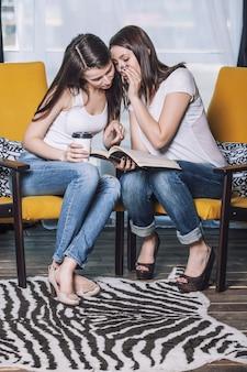 Mooie vrouwenvrienden die gelukkige glimlach onder de boeken thuis spreken