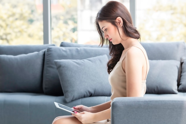 Mooie vrouwenzitting en online het winkelen met tablet in woonkamer.