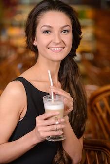 Mooie vrouwenzitting in een koffie met een kop van koffie latte.