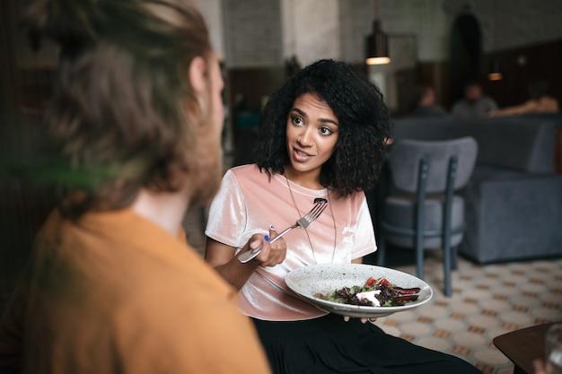 Mooie vrouwenzitting in restaurant en bespreek iets met vriend