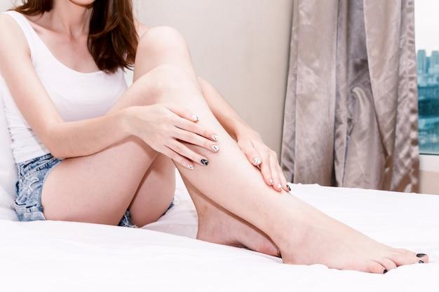 Mooie vrouwenzitting op bed en wat betreft haar huid op benen