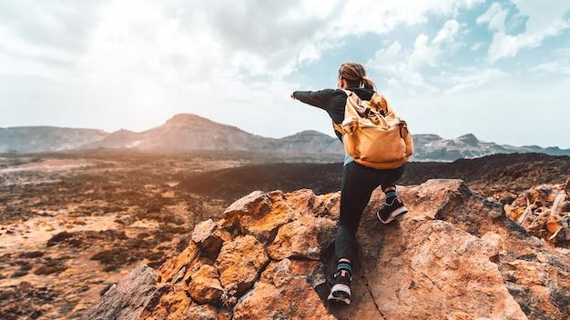 Mooie wandelaar vrouw op de top van de berg wijzend op de zonsondergang vallei. meisje met rugzak reist alleen in de natuur.
