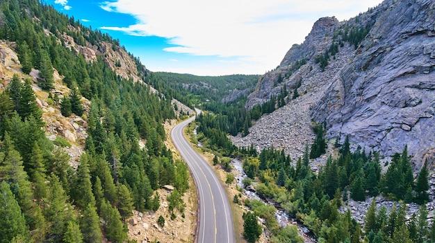 Mooie wegsnelweg door canyon naast landbergen en bos van pijnbomen
