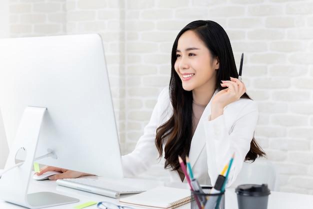 Mooie werkende vrouw die computer in het bureau met behulp van