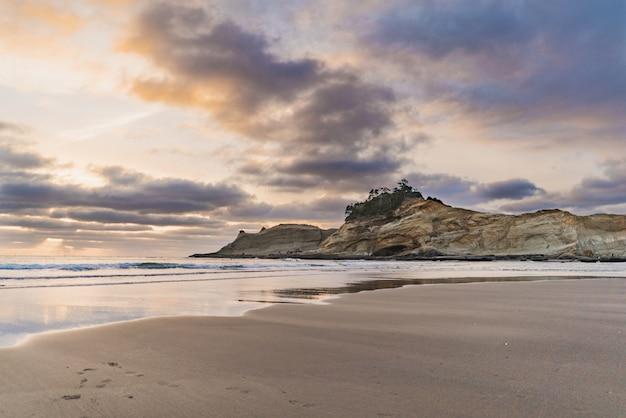 Mooie wide shot van een klif aan zee met een zanderige kust onder een hemel met wolken
