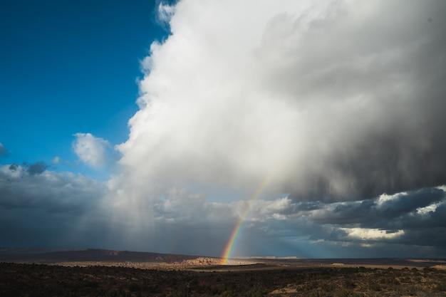 Mooie wide shot van een regenboog tussen witte wolken in een heldere blauwe hemel