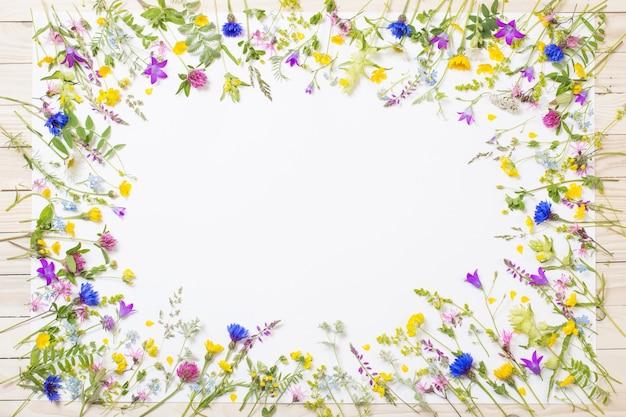 Mooie wilde bloemen op wit vel op houten achtergrond