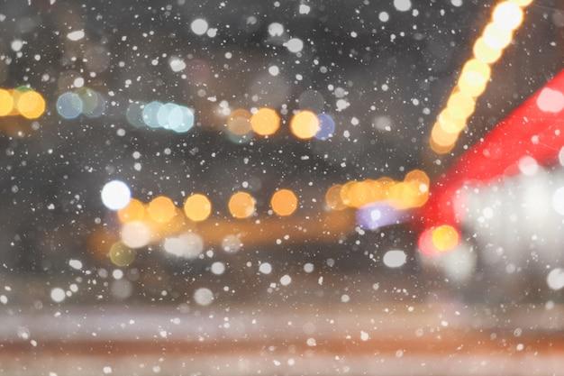 Mooie winter wazig achtergrond van nacht stad met vallende sneeuw en bokeh lichten