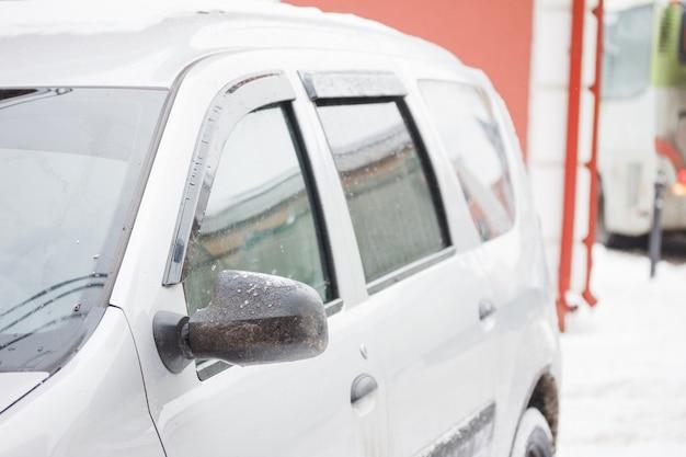 Mooie winterochtend besneeuwde auto op straat. zijspiegel achteraanzicht van de auto in het ijs in de winter