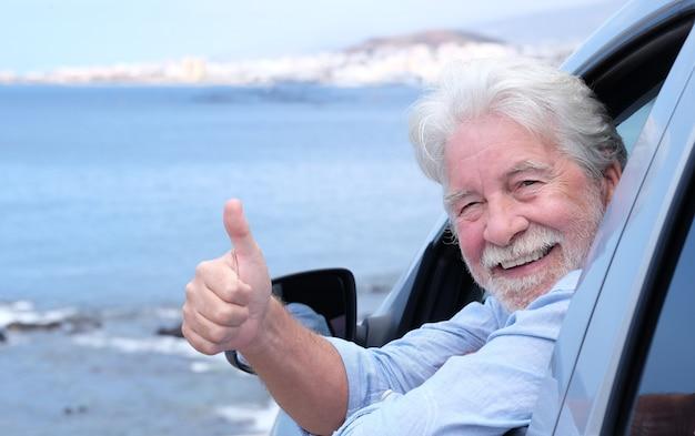 Mooie witharige senior man in de auto camera kijken met duim omhoog. lachende witharige ouderen genieten van vrijheid en pensioen. zeegezicht en blauwe lucht