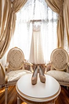 Mooie witte bruidsschoenen en jurk bij luxe slaapkamer