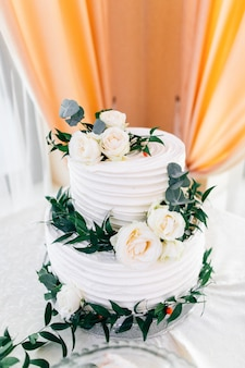 Mooie witte bruidstaart versierd met bloemen