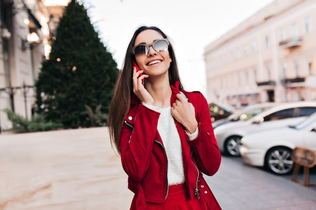 Mooie witte dame die geniet van een wandeling door de stad en telefoneert