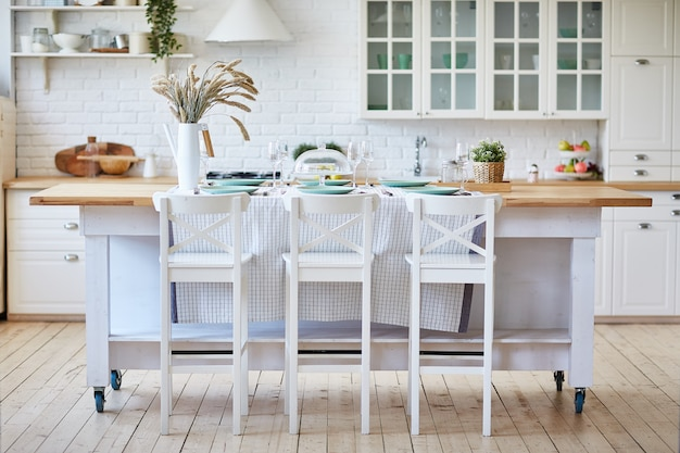 Mooie witte houten keuken met eilandtafel en stoelen.