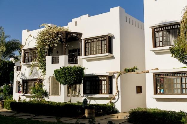 Mooie witte huizen aan de tropische tuin met palmen