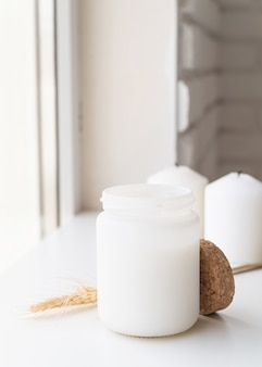 Mooie witte kaars met tarwespikes op wit oppervlak
