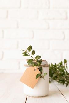 Mooie witte kaars met verse groene bladeren op witte houten oppervlak