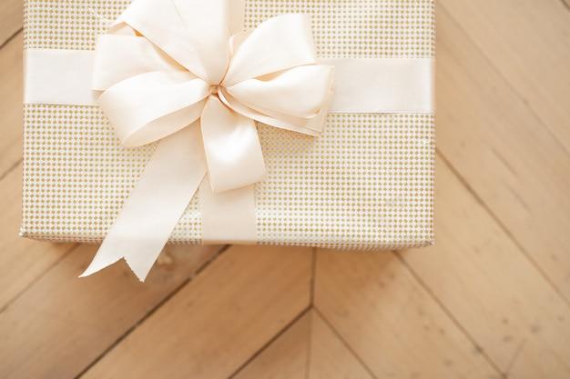 Mooie witte kerstdoos met een strik ligt op de grond