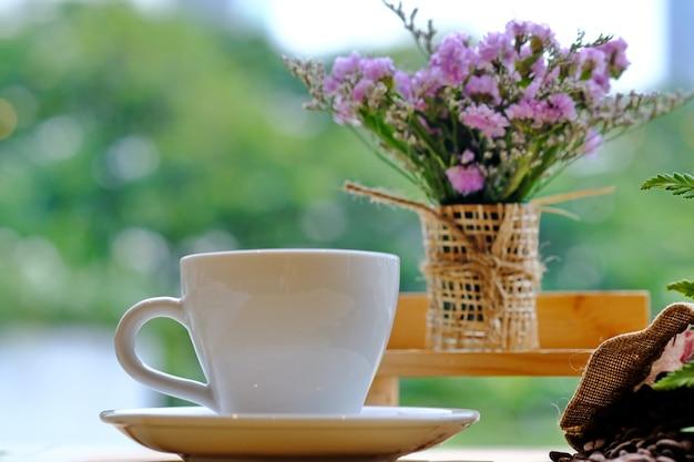 Mooie witte koffiekop op lijstbloemen op vaas vage achtergrond.