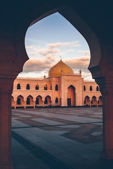 Mooie witte moskee in het licht van de zonsondergang. bekijk door de boog. bolghar, rusland.