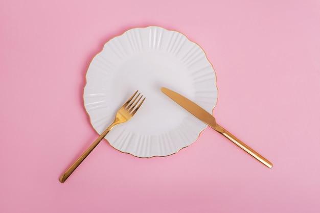 Mooie witte plaat met gouden mes en vork op roze achtergrond