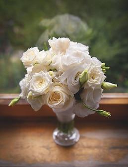 Mooie witte rozen in een glazen vaas in de buurt van venster.