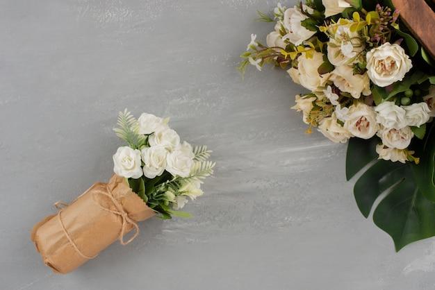 Mooie witte rozen op houten kist en in boeket op grijze ondergrond
