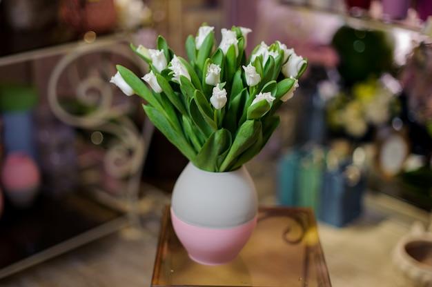 Mooie witte tulpen die zich in de blauwe en roze vaas bevinden