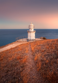 Mooie witte vuurtoren op de oceaankustlijn bij zonsondergang