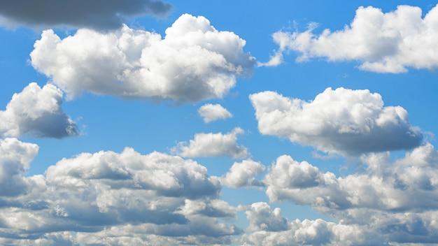 Mooie witte wolken die op blauwe hemel voor achtergrondenconcept drijven.