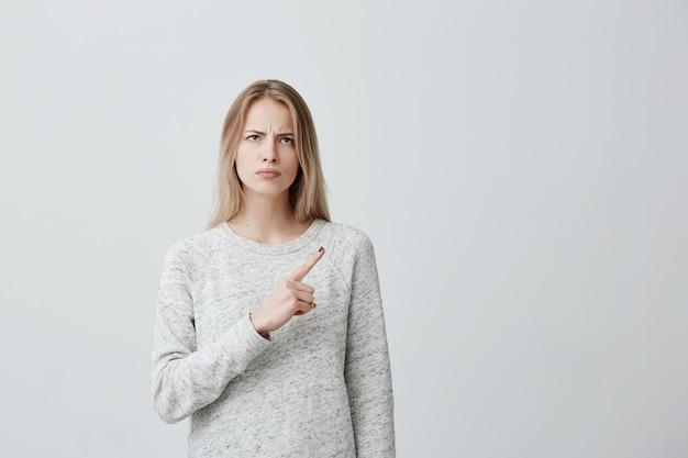 Mooie woedende vrouw die met blond geverfd haar zijwaarts met ernstige en boze uitdrukking kijkt die wijsvinger richt, die exemplaarruimte toont