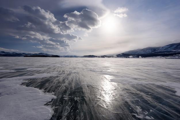 Mooie wolken boven het ijs oppervlak en winderige sneeuwjacht op een ijzige dag. bevroren baikalmeer.