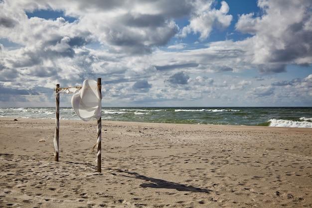 Mooie wolken en een door de wind waaiende trouwluifel op het zandstrand. huwelijksceremonie op het strand
