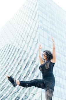 Mooie yogi-vrouw het beoefenen van yoga in de grote stad tussen gebouwen.