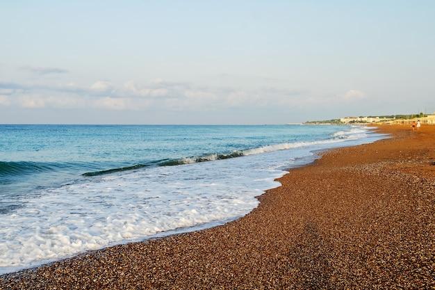 Mooie zachte zeegolf op het strand met kleine kiezelstenen en zand.