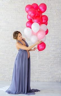 Mooie zachte zwangere vrouw met ballonnen
