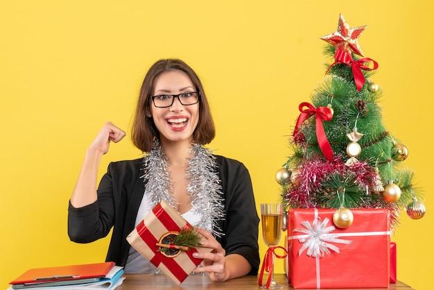 Mooie zakelijke dame in pak met bril toont haar kracht zittend aan een tafel met een kerstboom erop in het kantoor
