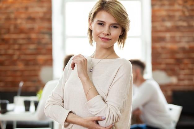 Mooie zakelijke dame kijkt naar de camera en glimlacht terwijl ze op kantoor werkt.
