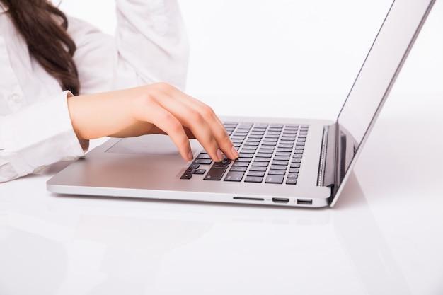 Mooie zakelijke vrouw glimlach zittend aan het bureau werken met behulp van laptop kijken naar het scherm, met de hand schrijven, geïsoleerd over witte muur