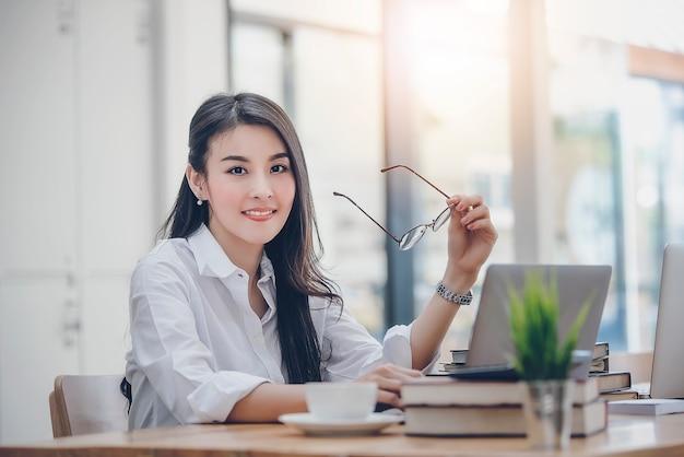 Mooie zakenvrouw bedrijf bril en zit aan haar bureau in office